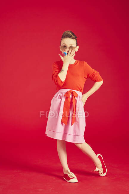 Brunette girl wearing in sunglasses and skirt, posing and standing on red background — Stock Photo
