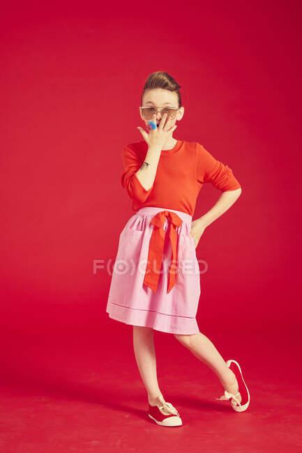 Брюнетка в солнцезащитных очках и юбке, позирует и стоит на красном фоне — стоковое фото