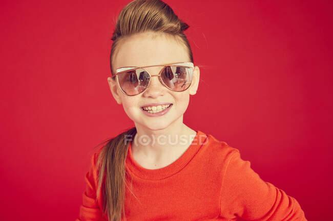 Счастливая улыбающаяся брюнетка в солнцезащитных очках и позирующая на камеру — стоковое фото