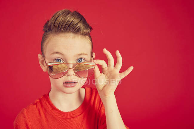Brunette girl wearing in sunglasses and posing on camera — Stock Photo