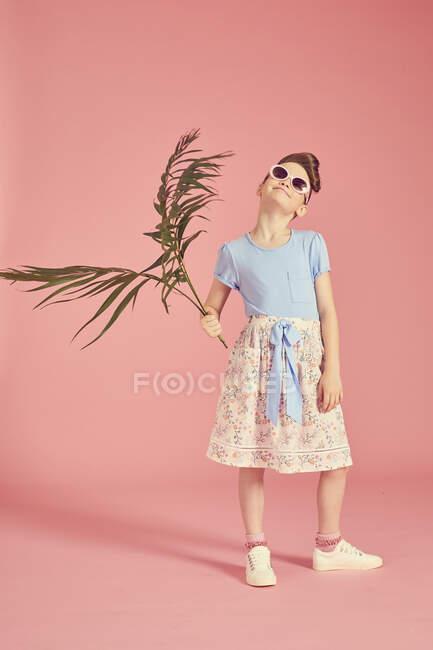 Longitud completa de chica morena en gafas de sol sobre fondo rosa, la celebración de la hoja de palma - foto de stock