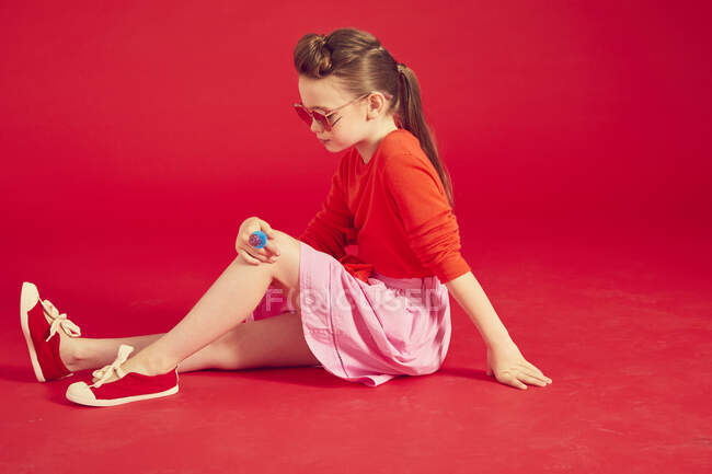 Brunette girl wearing in sunglasses and skirt, posing and sitting on red background — Stock Photo