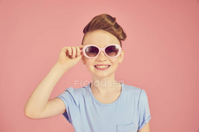 Portrait of brunette girl wearing blue T shirt and sunglasses on pink background, looking at camera. — Stock Photo