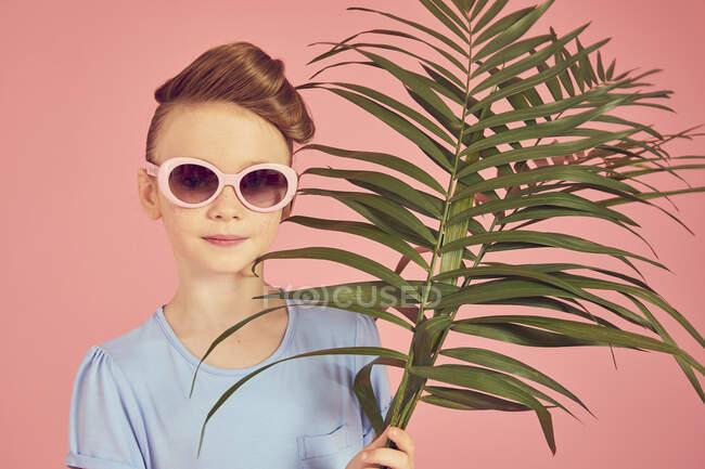 Retrato de chica morena en gafas de sol sobre fondo rosa, sosteniendo hoja de palma, mirando a la cámara - foto de stock