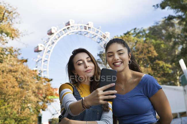 Deux jeunes femmes aux longs cheveux bruns debout dans un parc près d'une grande roue, prenant selfie avec téléphone portable. — Photo de stock