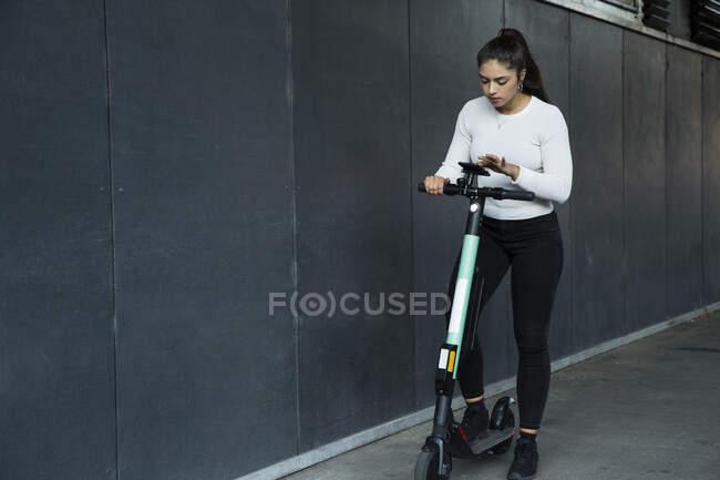 Junge Frau mit langen braunen Haaren steht auf Elektroroller. — Stockfoto