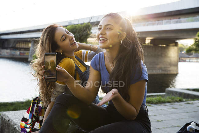 Two young women with long brown hair sitting on riverbank, holding mobile phone and smiling. — Stock Photo