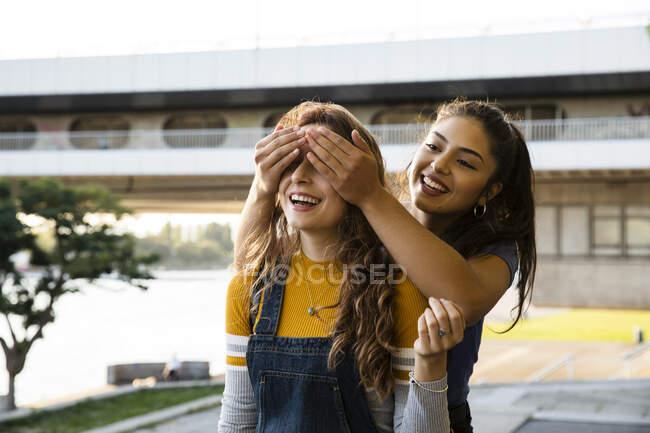 Deux jeunes femmes aux longs cheveux bruns debout sur le bord de la rivière, souriantes et couvrant les yeux. — Photo de stock