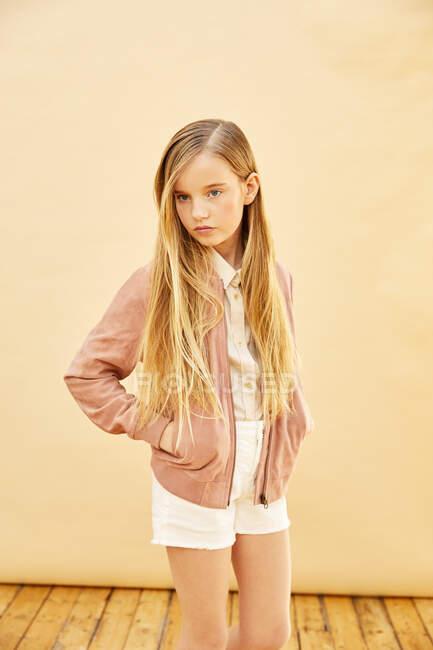 Портрет девушки с длинными светлыми волосами в шортах, рубашке и розовой куртке, на бледно-желтом фоне. — стоковое фото