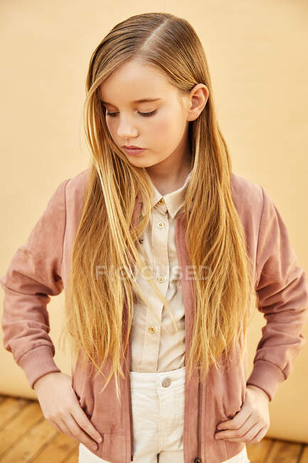 Портрет дівчини з довгим світлим волоссям у шортах, сорочці та рожевій куртці на блідо-жовтому тлі.. — стокове фото