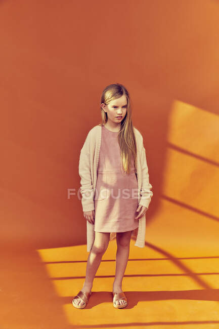 Portrait of girl with long blond hair wearing pink mini-dress and cream-coloured cardigan, on orange background. — Stock Photo
