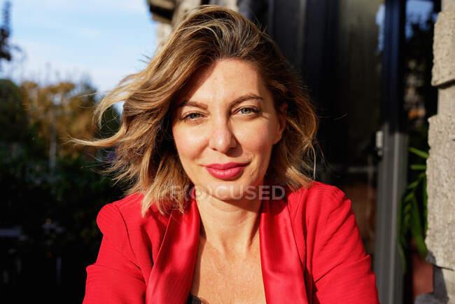 Портрет красивої ділової жінки в червоній куртці з білявим волоссям, дивлячись на камеру — стокове фото