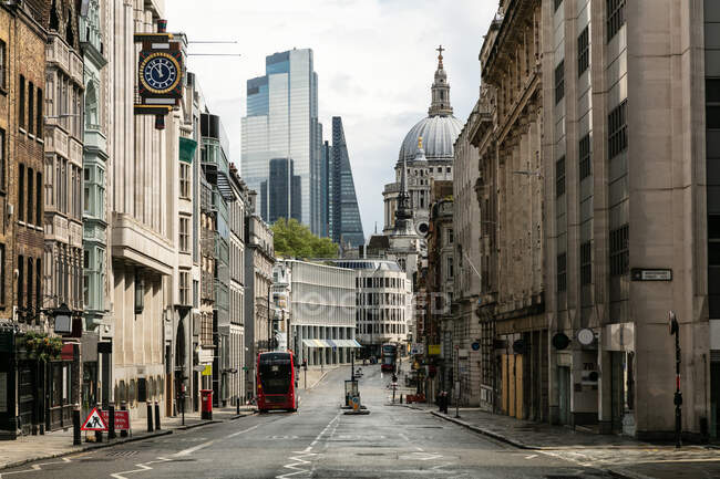 Vue le long de Fleet Street vide avec des immeubles de bureaux et la cathédrale Saint-Paul parmi les immeubles modernes de grande hauteur à Londres pendant la crise du virus Corona. — Photo de stock