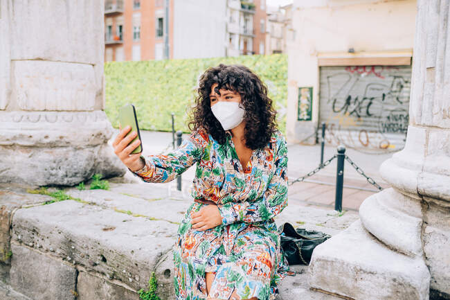 Young woman wearing face mask during Corona virus, sitting outdoors, taking selfie. — Stock Photo