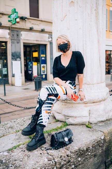 Jovem mulher usando máscara facial durante o vírus Corona, sentado ao ar livre, olhando para a câmera. — Fotografia de Stock
