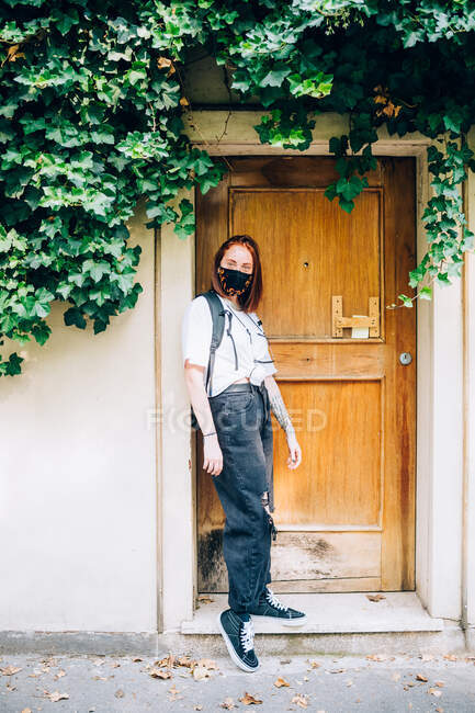 Young woman wearing face mask during Corona virus, standing outside front door of building, looking at camera. — Stock Photo