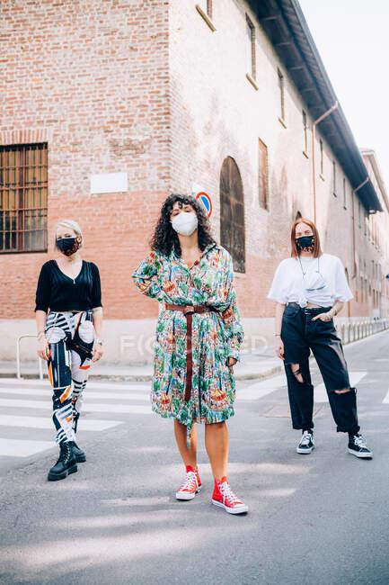 Три молодые женщины в масках во время Короны, стоящие на пешеходном переходе на улице. — стоковое фото