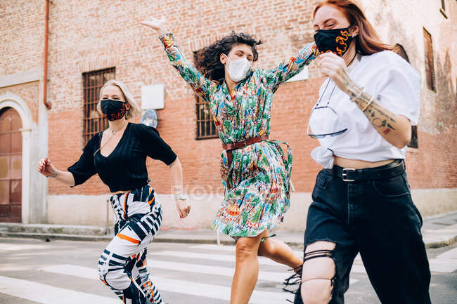 Three young women wearing face masks during Corona virus, running across a pedestrian crossing in a street. — Stock Photo