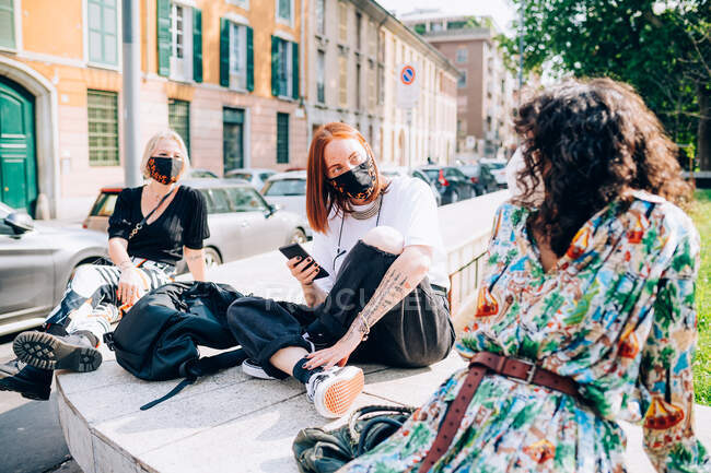 Three young women wearing face masks during Corona virus, sitting on a riverbank, chatting. — Stock Photo