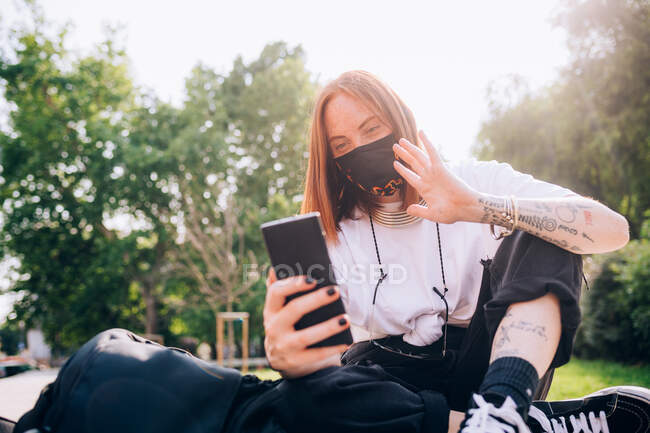 Young woman wearing face mask during Corona virus, sitting outdoors, checking mobile phone. — Stock Photo