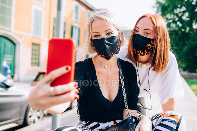 Two young women wearing face masks during Corona virus, sitting on a riverbank, taking selfie. — Stock Photo