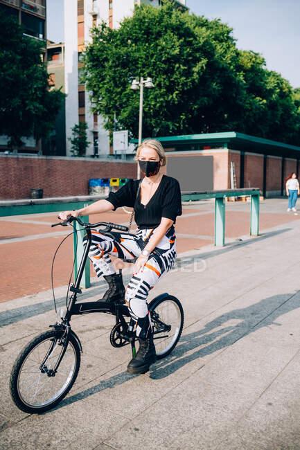 Giovane donna che indossa maschera facciale durante il virus Corona, in bicicletta sulla bicicletta pieghevole. — Foto stock