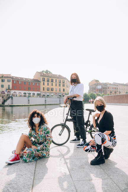 Три молодые женщины в масках во время Короны, стоят на берегу реки, смотрят в камеру. — стоковое фото