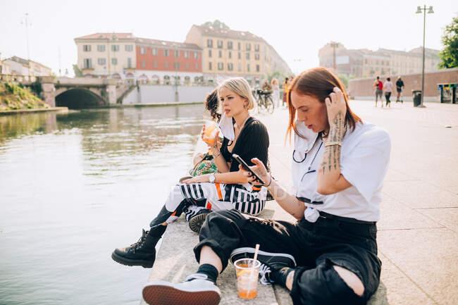 Tre giovani donne sedute su una riva del fiume, che bevono e usano il cellulare. — Foto stock