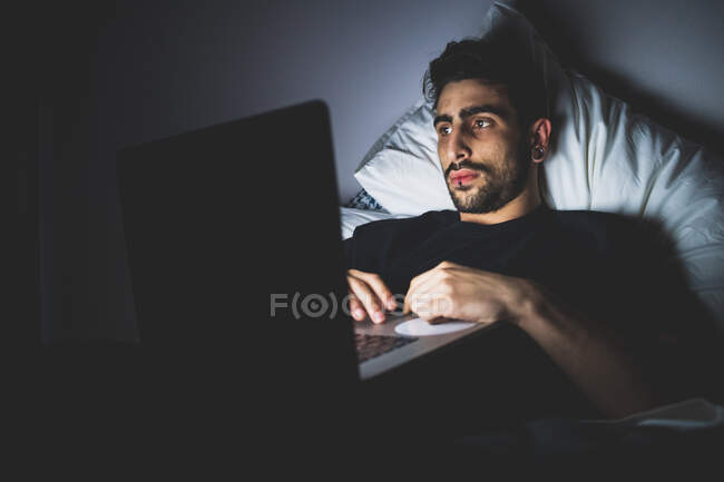 Bearded young man lying in bed at night, looking at laptop screen — Stock Photo