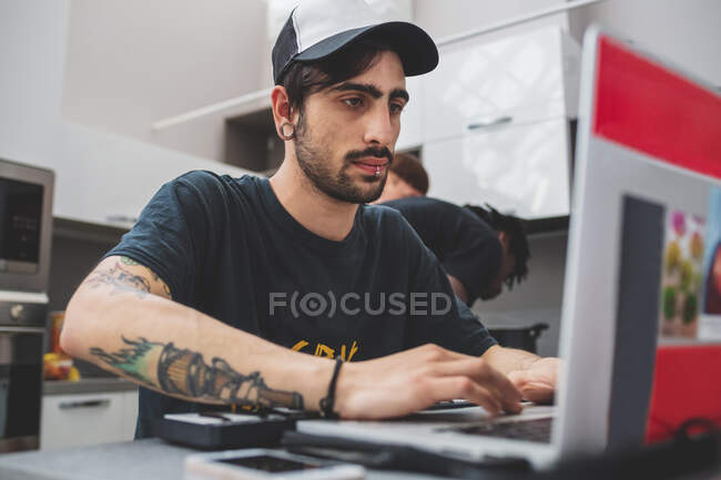 Young bearded man with piercings sitting at table, wearing baseball cap, typing on laptop — Foto stock