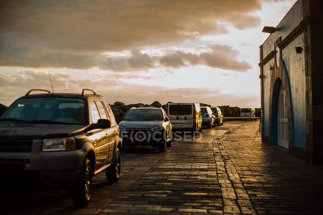 Ряд припаркованных машин на мощеной набережной в сумерках, облачное небо заката — стоковое фото