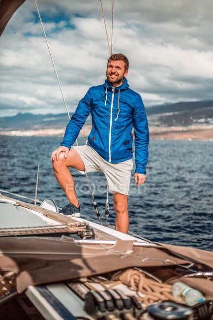 Портрет улыбающегося человека, стоящего на борту парусной яхты, отдыхающего на море — стоковое фото