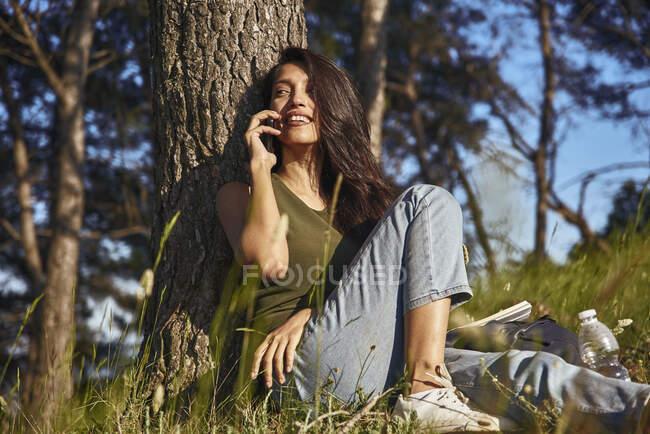 Retrato de jovem mulher sentada debaixo de uma árvore em uma floresta, falando no telefone celular — Fotografia de Stock