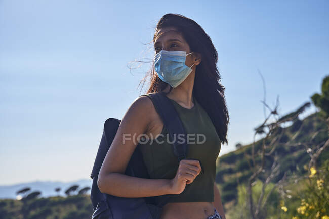 Young woman with long brown hair standing on hill carrying backpack and wearing face mask during Coronavirus Crisis — Stock Photo