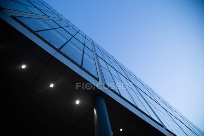 Низкоугольный вид на стеклянный фасад современного небоскреба. — стоковое фото