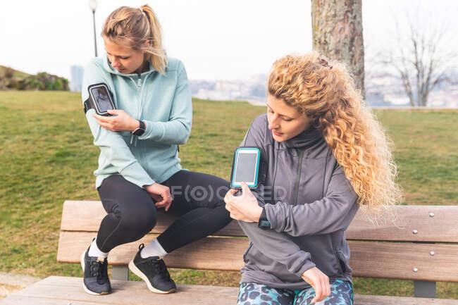 Due giovani donne con lunghi capelli biondi che indossano abbigliamento sportivo, sedute sulla panchina del parco dopo aver fatto jogging, controllano i loro telefoni cellulari. — Foto stock