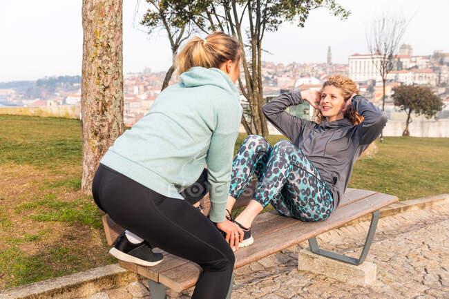 Zwei junge Frauen mit langen blonden Haaren in Sportbekleidung strecken sich nach dem Joggen auf einer Parkbank. — Stockfoto