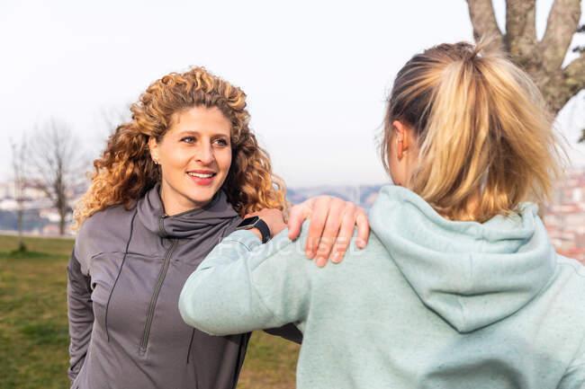 Deux jeunes femmes aux longs cheveux blonds vêtus de vêtements de sport, debout dans un parc, s'étirant après le jogging — Photo de stock