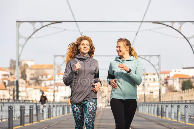 Две молодые женщины бегают по мосту Дома Луиса I в Порту, Португалия — стоковое фото