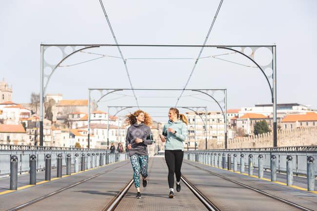 Дві молоді жінки біжать на Дон Луїс І мостом у Порто (Португалія)... — стокове фото