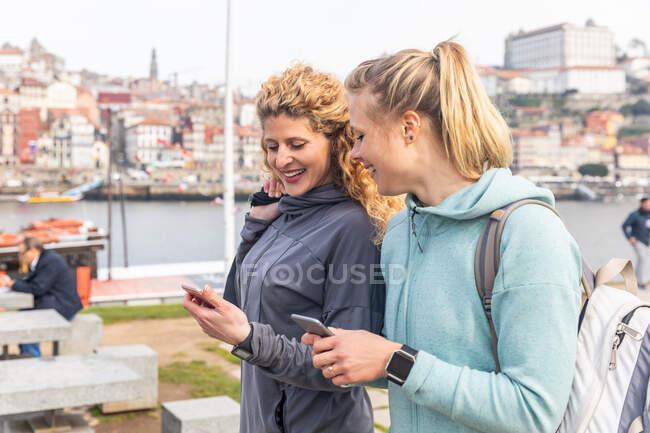Due giovani donne che camminano lungo il fiume Douro, controllando i loro telefoni, Oporto, Portogallo. — Foto stock