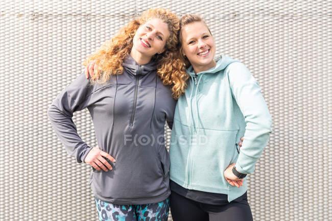 Deux jeunes femmes aux longs cheveux blonds portant des vêtements de sport, regardant la caméra. — Photo de stock