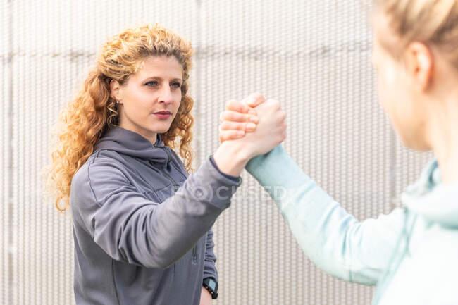 Дві молоді жінки з довгим світлим волоссям в спортивній манері, потискаючи руки після фізичних вправ.. — стокове фото