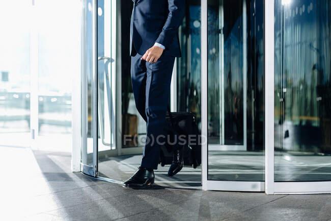 Бизнесмен с колесным багажом выходит из вращающихся дверей здания — стоковое фото