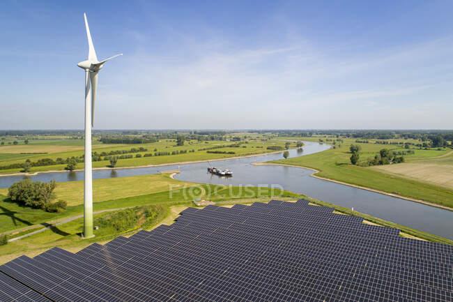 Solar panels and wind turbine near Ijssel river, The Netherlands. — Stock Photo