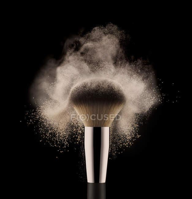 Primo piano di spazzola cosmetica in polvere su sfondo nero. — Foto stock