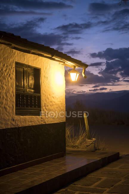 Lanterna illuminante cottage con pareti imbiancate e terrazza di notte. — Foto stock