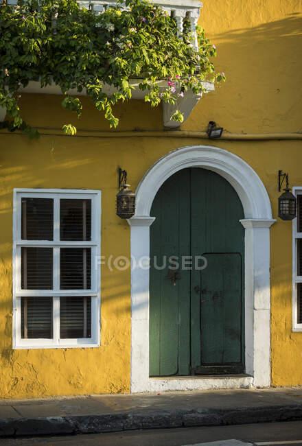 Colorato muro di casa gialla e porta d'ingresso verde nella città vecchia — Foto stock