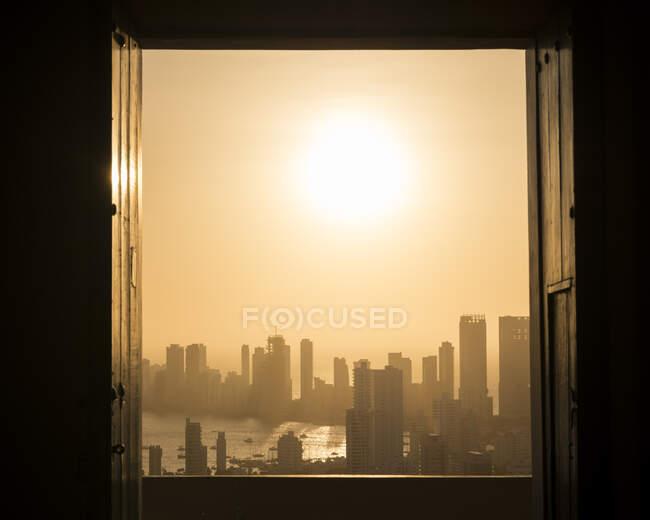 Vista attraverso una finestra sul paesaggio urbano e sul lungomare con cielo arancione nebbioso — Foto stock