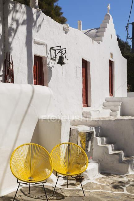 Duas cadeiras amarelas por uma casa caiada de branco, e uma torre sineira. — Fotografia de Stock